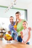 Семья есть свежие фрукты для здорового прожития в кухне Стоковое фото RF