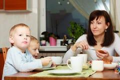 Семья есть хлопья мозоли и еду завтрака хлеба на таблице Стоковые Изображения