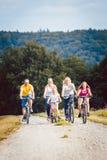Семья ехать их велосипеды на после полудня в сельской местности Стоковое фото RF