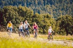 Семья ехать их велосипеды на после полудня в сельской местности Стоковое Изображение