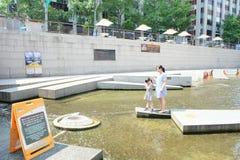 Семья делает желание для удачливого на потоке Cheonggyecheon, Южной Корее Стоковые Фотографии RF