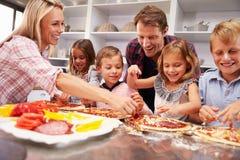 Семья делая пиццу для обедающего Стоковое Изображение