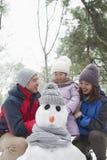 Семья делая снеговик в парке в зиме Стоковые Фотографии RF