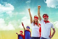 Семья замаскированная в superheros против предпосылки неба стоковое фото