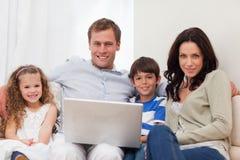 Семья занимаясь серфингом интернет в живущей комнате совместно Стоковые Изображения