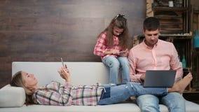 Семья занятая с электронными устройствами на софе сток-видео