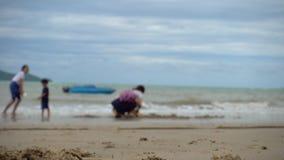 Семья играет на нерезкости пляжа с песком сток-видео