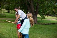 Семья играя бейсбол в парке Стоковое Фото