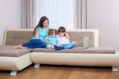 Семья играя видеоигру на умном телефоне Стоковое Изображение RF