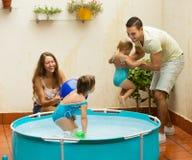 Семья играя в бассейне на террасе Стоковые Изображения RF