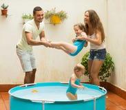Семья играя в бассейне на террасе Стоковые Фото