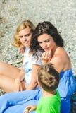 Семья играя и говоря на каменном пляже Стоковые Изображения