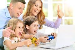 Семья играя на компьтер-книжке на таблице Стоковые Фотографии RF