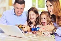 Семья играя на компьтер-книжке на таблице Стоковое Изображение