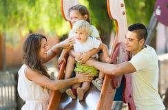 Семья играя на скольжении детей Стоковая Фотография RF