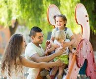 Семья играя на скольжении детей Стоковые Изображения RF