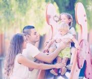 Семья играя на скольжении детей Стоковые Фотографии RF