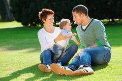 Семья играя на траве Стоковые Изображения