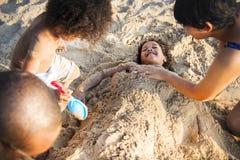 Семья играя совместно на пляже Стоковые Изображения