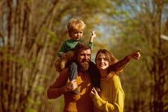 Семья играя с бумажным самолетом в парке Мальчик и родители играя игры совместно на открытом воздухе Этому самолету нужно лететь стоковое изображение rf