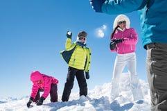 Семья играя с снежными комьями стоковое изображение rf