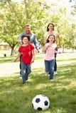 Семья играя футбол в парке Стоковые Изображения RF
