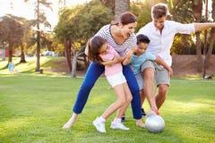 Семья играя футбол в парке совместно стоковая фотография rf