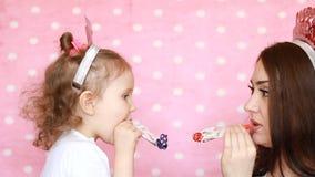 Семья - игра матери и дочери совместно, смех и дуя рожки день рождения счастливый Портрет молодой женщины и a сток-видео