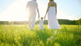 Семья идет в дочь парка и младенца предпринимая меры ее первые шаги Все одели в белизне и под заходящим солнцем