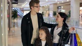 Семья идет в торговый центр, они стоит около внешней витрины магазина и взгляда на одеждах сток-видео