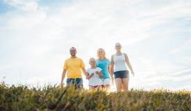 Семья идя в заход солнца над лугом лета Стоковая Фотография RF