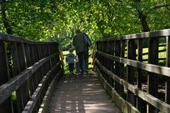 Семья идя за деревянный мост на солнечный день стоковые изображения rf