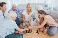 Семья из нескольких поколений играя шахмат стоковая фотография