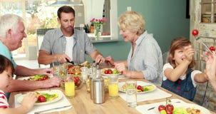 Семья из нескольких поколений имея обедающий