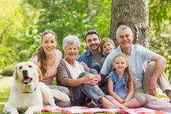 Семья из нескольких поколений при их собака сидя на парке стоковая фотография rf