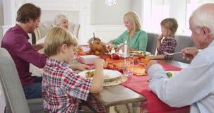 Семья из нескольких поколений сидя вокруг таблицы для еды благодарения - бабушка делает короткую речь прежде чем они начинает съе акции видеоматериалы