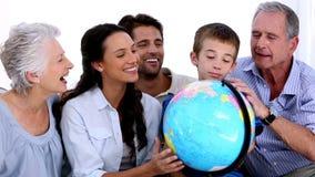 Семья из нескольких поколений смотря глобус совместно видеоматериал