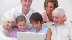 Семья из нескольких поколений смотря компьтер-книжку видеоматериал