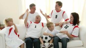 Семья из нескольких поколений с дедами на футболе софы наблюдая акции видеоматериалы