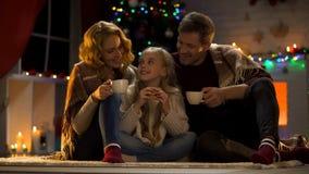 Семья из трех человек выпивая горячее какао около рождественской елки, радуясь счастливые праздники стоковое изображение rf