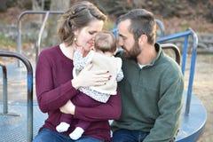 Семья из трех человек на парке осенью на веселом идет круг Стоковая Фотография