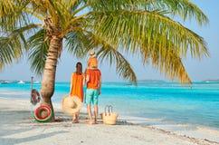 Семья из трех человек на пляже под пальмой стоковые фото