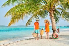 Семья из трех человек на пляже под пальмой стоковая фотография