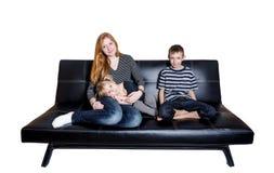 Семья из трех человек на кресле изолированном на белой предпосылке Стоковые Изображения