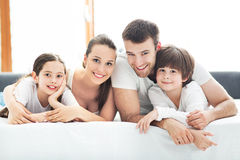Семья из четырех человек лежа на кровати стоковые фото
