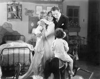 Семья из четырех человек стоя совместно в комнате ребенка (все показанные люди более длинные живущие и никакое имущество не сущес Стоковое Фото