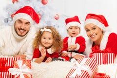 Семья из четырех человек с настоящими моментами и рождественской елкой Стоковые Изображения RF