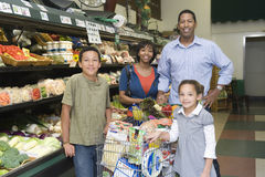 Семья из четырех человек ходя по магазинам в супермаркете Стоковое фото RF