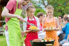 Семья имея барбекю на приём гостей в саду стоковая фотография