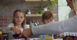 Семья имея еду на обеденном столе в кухне на удобном доме 4k акции видеоматериалы